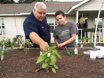 Prentice Shew, a Global Gardens volunteer, assists a student at Union Middle School in Tulsa, Oklahoma with the school's new aquaponics system. (photo courtesy Prentice Shew/Global Gardens)
