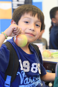 A Riverside Unified School District student holds up an apple which he is about to eat. Through the efforts of Rodney Taylor and others, students in the Riverside Unified School District are actively encouraged to eat more fruits and vegetables. (photo courtesy of Rodney Taylor/Riverside Unified School District)
