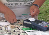 Information is entered into an EBT payment processor after the card is swiped.  Credit: Illinois Farmers Market Association