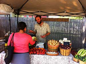Kevin Prather, Mellowfields Urban Farm and Common Ground urban farmer, sells his produce at the Cottins Hardware Farmers Market. Image credit: Eileen Horn