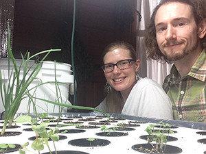 Ruth and Noah Smucker are seen next to a small aquaponics system inside their home in Goshen, Indiana. They plan to install a larger enclosed aquaponics system in their yard, with their eyes on even further expansion. (photo courtesy of Noah and Ruth Smucker)