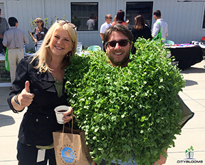 """Nick Halmos, founder and CEO of Cityblooms, is seen in his """"pea-shoot suit"""" at the headquarters of Plantronics, where Cityblooms grows hydroponic vegetables and greens for Plantronics employees. (photo courtesy of Nick Halmos)"""