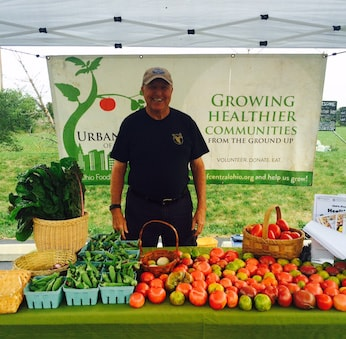 A volunteer mans a pay-what-you-can produce stand at Wheatland Farms, one of two urban farms in Grove City, Ohio that are part of the Mid-Ohio Foodbank's Urban Farms of Central Ohio initiative. Photo courtesy of Mid-Ohio Foodbank.